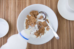Adding milk on cornflake Royalty Free Stock Image