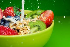 Adding milk to muesli with fruits breakfast Stock Images