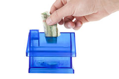 Adding money in blue house bank Stock Image