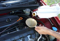Adding Motor Oil to Car. Male adding oil with a funnel after an oil change. Dipstick is nearby Royalty Free Stock Photos