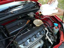 Adding Motor Oil to Car. Male adding oil with a funnel after an oil change. Dipstick is nearby Royalty Free Stock Image