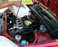 Adding Motor Oil to Car. Male adding oil with a funnel from the left side of a red car after a do-it-yourself oil change. Dipstick is nearby Stock Image