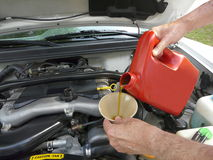 Adding Motor Oil to Car. Male adding oil with a funnel to a white car after an oil change. Dipstick and cap are nearby Royalty Free Stock Photo