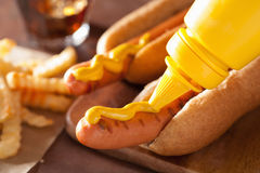 Adding mustard to grilled hot dog.  royalty free stock images