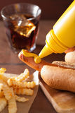 Adding mustard to grilled hot dog Royalty Free Stock Photo