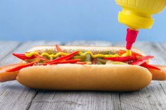 Adding mustard. To very spicy hot dog with red chili pepper , jalapeno and salsa sauce Royalty Free Stock Image
