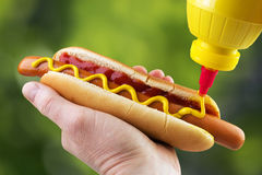 Adding mustard. Adding yellow mustard to hot dog in hand Royalty Free Stock Photos