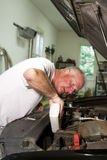 Adding Oil. Man performing routing maintenance by adding oil to an automobile in a home garage Royalty Free Stock Image