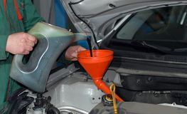 Adding Oil to a Car. Male adding oil with a funnel from the left side of a grey car stock photo