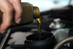 Adding Oil to a Car. Man's hand holding a bowl of motor oil and poured into the engine Stock Photos