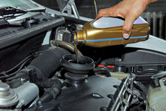 Adding Oil to a Car. Man's hand holding a bowl of motor oil and poured into the engine Royalty Free Stock Photos