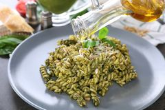 Adding oil to pasta with basil pesto sauce Royalty Free Stock Image
