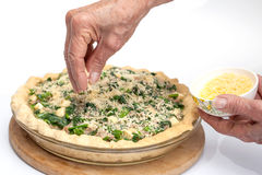 Adding parmesan cheese to the spinach and tuna quiche lorraine Stock Photos