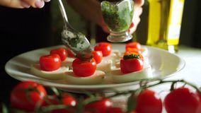Adding pesto sauce to mozzarella and tomato salad Caprese . Part of the set stock video