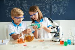 Adding reagent. Girl pouring reagent into flask with yellow reagent her classmate holding Stock Photos