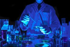 Adding reagent. Scientist adding reagent to petri dish in dark laboratory Royalty Free Stock Images