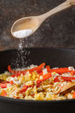 Adding salt in the pan with rice and bell pepper vertical Stock Images