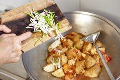 Adding scallion. Or spring onion to the cooking on the wok Stock Photos