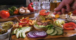 Adding a slice of tomato over a cheesburger with beer and French fries Stock Images