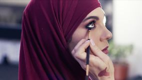 Adding some more eyeliner on the waterline of a gorgeous girl`s eyes. Stunningly beautiful female wearing purple hijab stock video footage