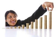 Adding some more to my investment profit. A young Asian businesswoman adding some coins to the highest stack in the most right row. Twelve stack represent twelve Stock Photo