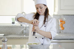 Adding some pepper to a dish. Cute female chef adding some pepper and condiments to a dish royalty free stock photography