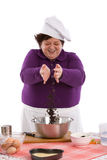Adding some raisins. Happy chef throwing a handfull of raisins in the mixing bowl Stock Photo