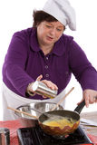 Adding some salt. Female chef adding some salt to her mixture in the wok royalty free stock photos