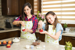 Adding some sprinkles to their cupcakes. Cute couple of mother and daughter adding some sprinkles to their freshly baked cupcakes in the kitchen royalty free stock photos