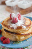 Adding some sugar. Delicious fresh pancakes being topped with icing sugar Royalty Free Stock Images