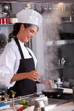 Adding some water. Professional chef in the kitchen adding some water to her dish Royalty Free Stock Image
