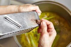Adding spices and herbs. Adding spices and herb to the chicken stock soup Stock Photos