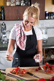 Adding sugar. Young attractive woman in the kitchen adding sugar to her strawberry sandwich stock images