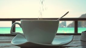 Adding sugar to Coffee In Glass Mug With Seaview. stock footage