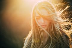 Adding volume to her long hair. Sensual woman with wavy long hair outdoor. Pretty girl with beautiful healthy hair in royalty free stock photo