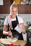 Adding water into the dough. Pretty female chef adding water to the flour royalty free stock image