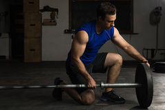 Adding weights to a barbell. Good looking and strong young man adding some weight plates to a barbell before exercising in a gym Royalty Free Stock Photography