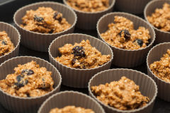 Adding wheat bran muffins mix to the baking cups Royalty Free Stock Image