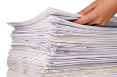 Adding work. Hand adding more files to a large stack of documents Stock Image