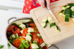 Adding zucchini pieces into saucepan Royalty Free Stock Images