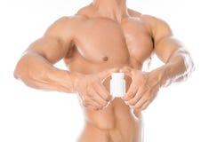 Additifs de bodybuilding et de produit chimique : le bodybuilder fort beau tenant un pot blanc de pilules sur le blanc a isolé le image libre de droits
