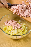 Addition of boiled wurst in salad. Addition of the cut boiled wurst in salad Royalty Free Stock Photo