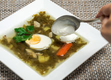 The addition of sour cream in soup. Sorrel soup in a white square plate and spoon with sour cream stock photo
