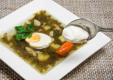 The addition of sour cream in soup. Sorrel soup in a white square plate and spoon with sour cream stock image