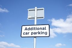 Additional car parking sign against blue sky. Uk royalty free stock image