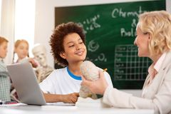 Delighted positive boy having a tutoring lesson. Additional knowledge. Delighted positive boy listening to his teacher while having a tutoring lesson stock photo