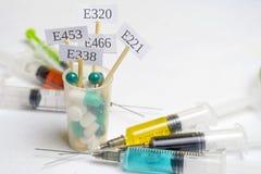 Additivi alimentari nocivi In un vetro con delle le pillole colorate multi sono i piatti con i E-supplementi di codice Vicino son fotografie stock libere da diritti