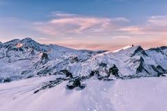 Addolcisca la luce rosa del tramonto alle montagne delle alpi dell'inverno Immagine Stock
