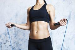 Addome femminile Donna muscolare con il salto della corda sulla parete strutturata immagini stock libere da diritti