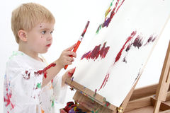addorable boy easel painting toddler 库存照片